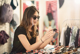Woman choosing sunglasses in the store. - 212928221