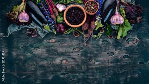 Fioletowe jedzenie. Świeże warzywa i jagody. Na drewnianym tle. Widok z góry. Skopiuj miejsce.