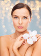 wellness and beauty concept - beautiful bare woman with orchid flower over holidays lights background
