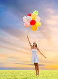happiness, summer and people concept - smiling young woman wearing sunglasses with balloons on meadow over sunset sky background - 212947804