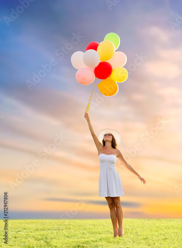 Leinwanddruck Bild happiness, summer and people concept - smiling young woman wearing sunglasses with balloons on meadow over sunset sky background