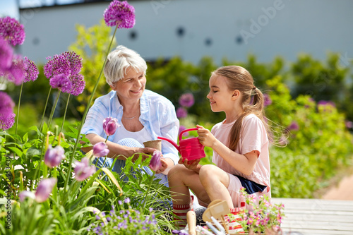 Leinwanddruck Bild gardening, family and people concept - happy grandmother and granddaughter planting flowers at summer garden