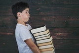 child with pile of books on wooden background - 212961677