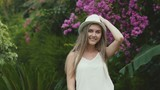 Portrait of pretty girl in hat posing at camera on flower bushes background - 212963298
