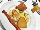 Breakfast meal with hashbrowns, eggs, bacon and croissant - 212973668