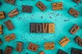 Love Spelled in Wooden Type Set Block Letters on a Turquoise Background - 212975094
