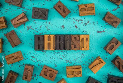 Christ Spelled in Wooden Type Set Block Letters on a Turquoise Background