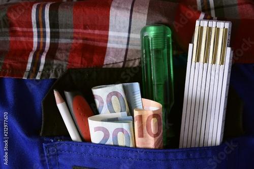 Leinwanddruck Bild Handwerker mit Werkzeug und Geldscheinen in der Hosentasche