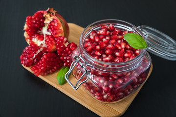 Delicious pomegranate seeds placed in glass jar with fresh organic pomegranates on rustic wooden background.Close up,Copy space