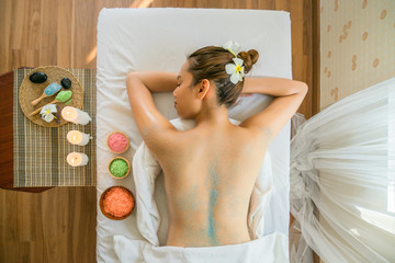 Young beautiful Asian woman relaxing  in the Spa. Brunette Getting a Salt Scrub Beauty Treatment in the Health Spa. . © tool51