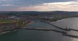 Aerial footage of Whitby Harbour, Whitby, United Kingdom.  Whitby Abbey can be seen on the cliff top. Looking inland from the North Sea. - 212987445