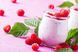 Raspberry smoothie with berry and yogurt on pink background, selective focus