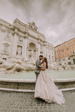 Bride and groom posing in front of Trevi Fountain (Fontana di Trevi), Rome, Italy - 213000839