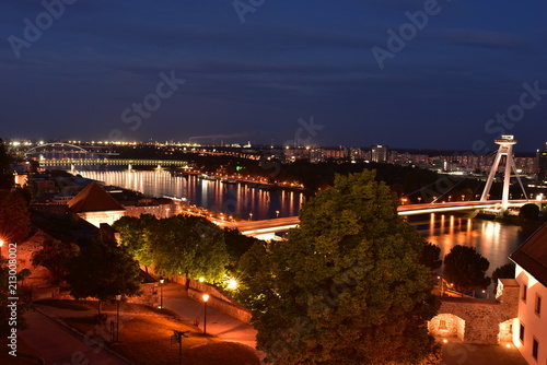 Foto Spatwand UFO View on New bridge over Danube river from castle hill in Bratislava,Slovakia after sunset