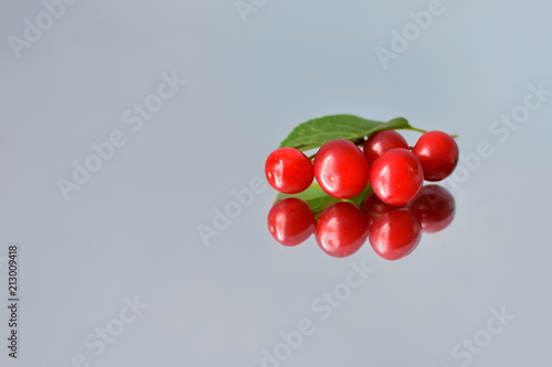 Foto Murales berries of ripe cherries and their reflection on a mirror surface