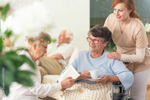 Two senior pensioners enjoying their leisure time together inside a private nursing home. Tender caretaker in uniform standing next to them - 213011405