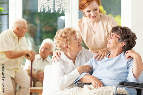 Foto Murales Happy friendship in old age. Tender caregiver standing behind senior women hugging each other in a nursing home. Men in the blurred background.