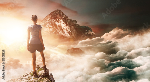 Hiker on peak with tall mountain in background