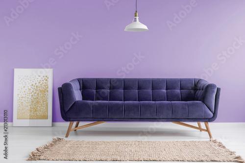 Fioletowa, aksamitna sofa i beżowy dywanik w pastelowym wnętrzu w stylu lawendy z makietą plakatu. Prawdziwe zdjęcie.