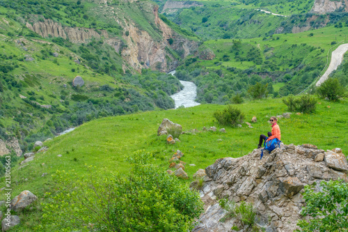Aluminium Pistache Young woman standing with a backpack in a mountain valley.