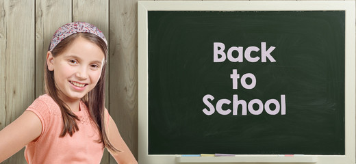 back to school written on blackboard with young girl