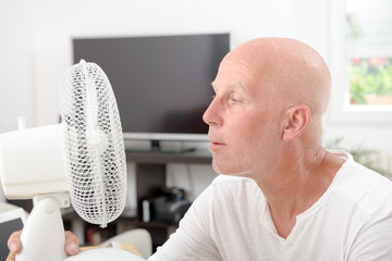 mature man refreshed with a fan