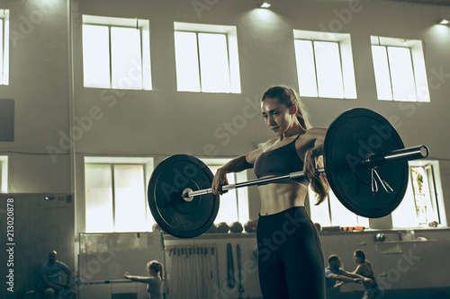 Fit young woman lifting barbells working out in a gym © master1305