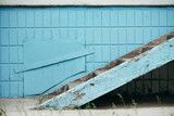 Blue wall of building with hatch and stairway close up. Steps against wall of blue tiles. Background with porch with copy space. - 213022240