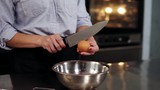 Pastry confectioner is separating whites from yolks, close-up. She is breaking it by knife and putting in steel bowl. Slow motion footage - 213022484