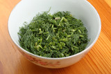 Ceramic bowl with chopped dill leaves on a table - 213026024
