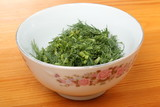Ceramic bowl with chopped dill leaves on a wooden table - 213026025