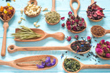 Black, fruit, cornflower, hibiscus, wild rose, white lotus and rooibos tea in wooden spoons on blue background