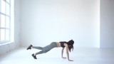 Sportive woman is warming up by walking on hands and legs with one lifted up. 4k. Studio lcoation. - 213034866