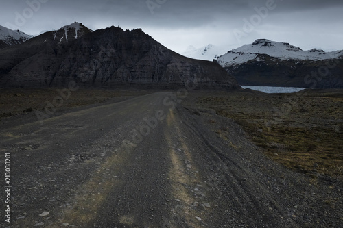 Gravel road is heading toward mountains in Iceland - 213038281