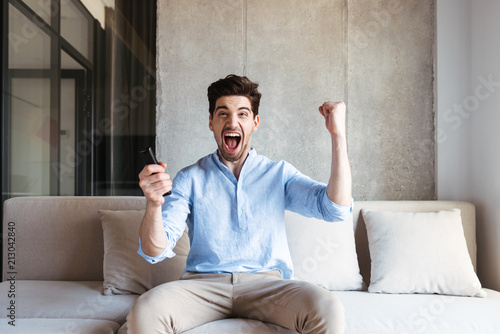 Leinwanddruck Bild Happy young man holding TV remote