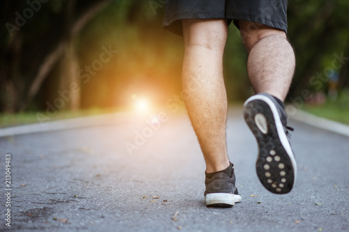 Starting day from morning jog. Full length rear view of young man in sports clothing jogging in park.Man in jogging shoes ready for a run outside at sunset