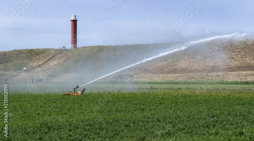 Fotobehang Blauwe hemel Spraying water on the fields behind the dunes of Julianadorp. Agriculture. Irrigation.