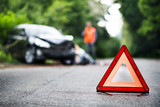 A close up of a red emergency triangle on the road in front of a car after an accident. - 213052254