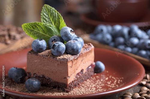 Leinwanddruck Bild Chocolate cake with blueberries and mint .