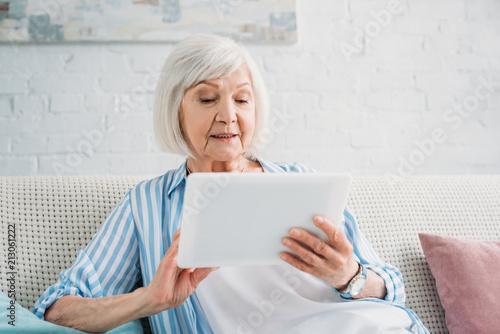 Leinwanddruck Bild portrait of senior woman using tablet on sofa at home