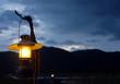 Leinwanddruck Bild - orange light from Burning old lantern illuminated at mountain sunset time.