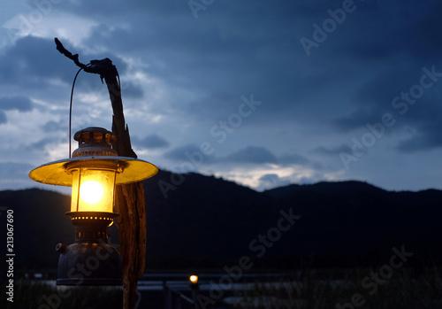 Leinwanddruck Bild orange light from Burning old lantern illuminated at mountain sunset time.