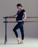 Young beautiful pregnant ballerina is posing in studio - 213071412
