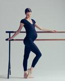 Young beautiful pregnant ballerina is posing in studio - 213071617