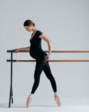 Young beautiful pregnant ballerina is posing in studio - 213071671