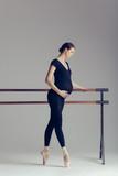 Young beautiful pregnant ballerina is posing in studio - 213071844