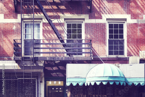 Foto Murales Building facade with fire escape, one of the New York City symbols, vintage color toning applied, USA.