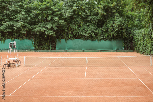 Genial View Of Brown Tennis Court With Chairs And Tennis Net
