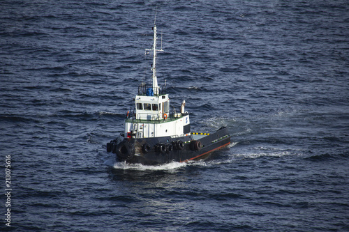 Tug boat, white and black, sailing by the sea