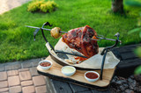 pigs with an apple on a sword; ready shank in the open air; a few leuces lie around the meat; cooked meats - 213076864